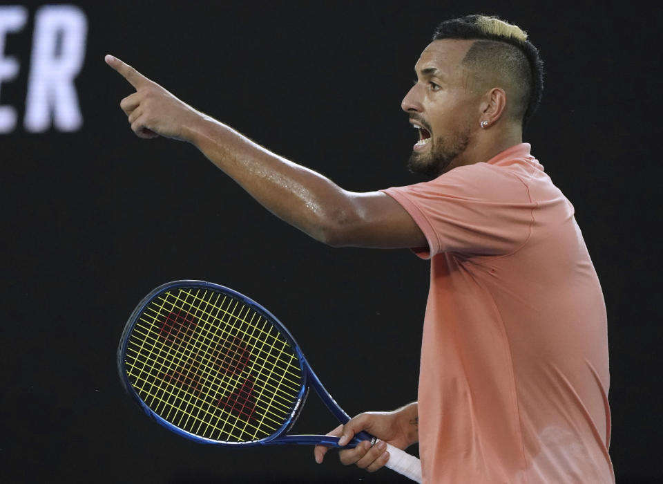 Australia's Nick Kyrgios points with a racket.
