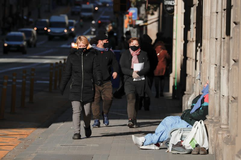A homeless man sits on the street during a cold wave, in Barcelona