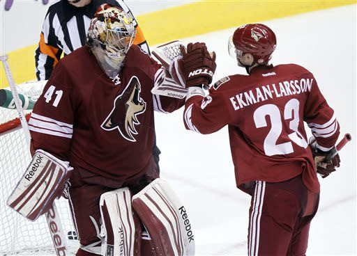 Phoenix Coyotes goalie Mike Smith, left, is congratulated by Oliver Ekman-Larsson, right, of Sweden, after Smith earned a shutout against the Colorado Avalanche in an NHL hockey game Saturday, April 6, 2013, in Glendale, Ariz. The Coyotes won 4-0. (AP Photo/Paul Connors)