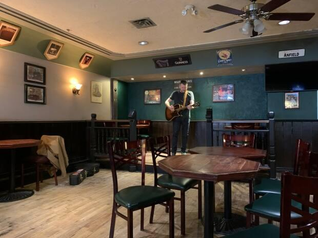 Patrick Jacobson, a Yellowknife musician and owner of YK Rocks, plays his guitar to an empty Black Knight Pub. (Alice Twa/CBC - image credit)
