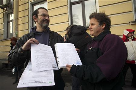 Greenpeace activist Dimitri Litvinov (L) and Peter Willcox, captain of the Greenpeace ship Arctic Sunrise, show papers certifying the termination of prosecution after they walked out of the offices of the Federal Migration Service Department in St. Petersburg, December 25, 2013. REUTERS/Stringer