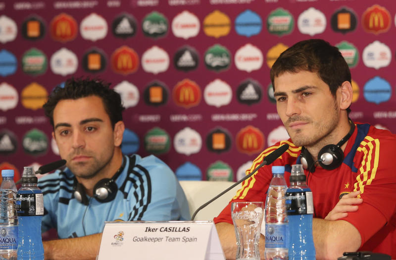 In this handout image provided by UEFA Spain's Xavi Hernandez, left, and Spain goalkeeper Iker Casillas talk to the media during a Euro 2012 soccer championship press conference at the Olympic Stadium in Kiev, Ukraine, Saturday, June 30, 2012, on the eve of the final between Spain and Italy. (AP Photo/UEFA via Getty Images)