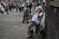 An older woman shields her ears during a protest of organizers and fans of music festivals stage against the government's COVID-19 restrictions on large-scale outdoor events, in Amsterdam, Netherlands, Saturday, Aug. 21, 2021. On Saturday, the festivals came to music fans as hundreds of performers and festival organizers held demonstration marches through six Dutch cities to protest what they argue are unfair restrictions that have forced the cancellation of summer festivals and other events.(AP Photo/Peter Dejong)