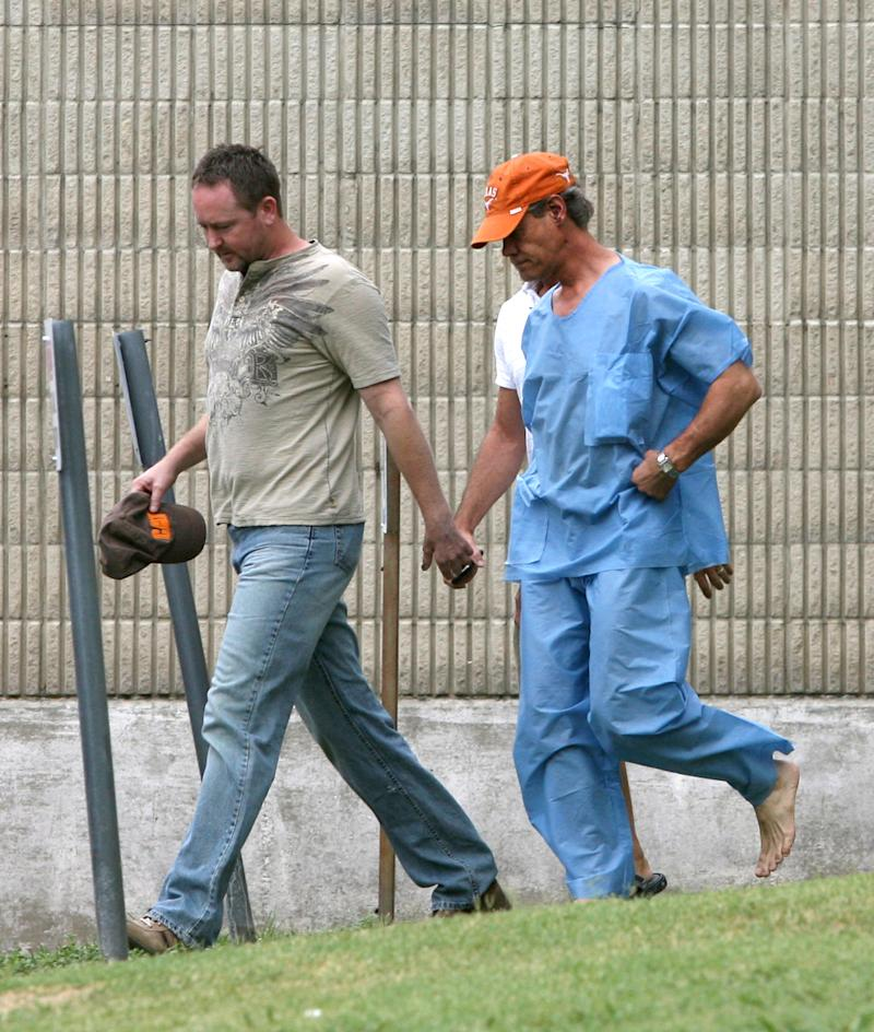 Randy Travis, far right exits the Grayson County jail with an unknown person Wednesday Aug. 8, 2012, in Sherman, Texas, after being arraigned on charges of driving while intoxicated and retaliation. (AP Photo/The Herald Democrat, Chris Jennings) TV OUT; MAGS OUT; TV AND MAGAZINE CALL FOR RATES TERMS; MANDATORY CREDIT