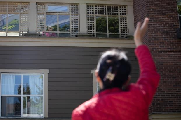 Laura Saimoto waves to her mother from outside the Sunrise of Vancouver retirement home on May 7, 2020.