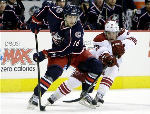 Columbus Blue Jackets' Derick Brassard, left, carries the puck across the blue line as Phoenix Coyotes' Ray Whitney defends during the second period of an NHL hockey game on Tuesday, March 6, 2012, in Columbus, Ohio. (AP Photo/Jay LaPrete)