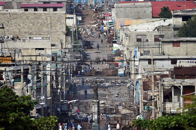 A Port-au-Prince street is seen full of debris and barriers on November 21, 2018, during a third day of strikes (AFP Photo/HECTOR RETAMAL)