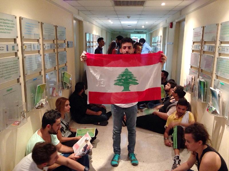 A Lebanese activist holds a national flag in a hallway during a surprise sit-in at Lebanon's environment ministry to demand the minister's resignation after mass protests over nationwide trash collection crisis on September 1, 2015 in Beirut (AFP Photo/)