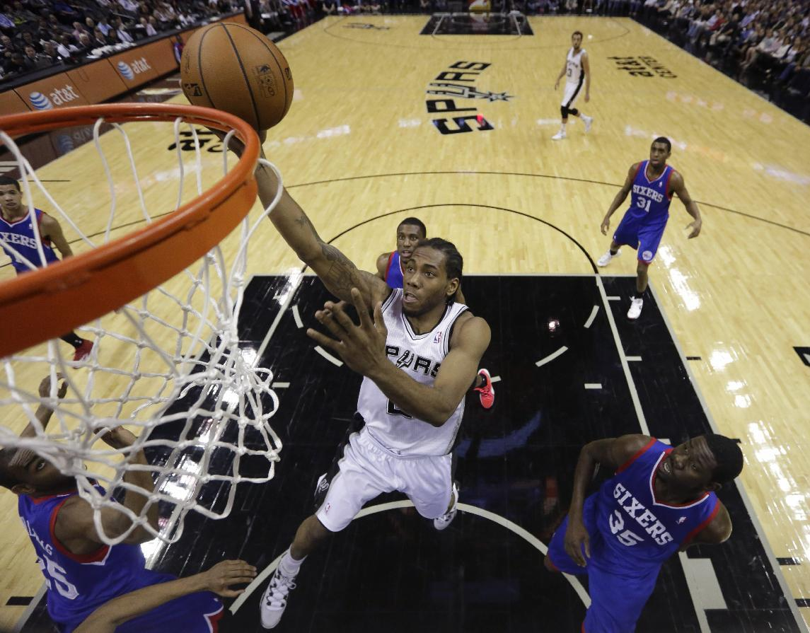 San Antonio Spurs' Kawhi Leonard, center, over 76ers' Elliot Williams (25) and Henry Sims (35) during the first half of an NBA basketball game, Monday, March 24, 2014, in San Antonio. (AP Photo/Eric Gay)