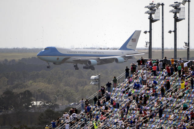 Fans watch from the grandstands as Air Force One, carrying President Donald Trump, prepares to land at Daytona International Airport before the NASCAR Daytona 500 auto race at Daytona International Speedway, Sunday, Feb. 16, 2020, in Daytona Beach, Fla. (AP Photo/Phelan M. Ebenhack)