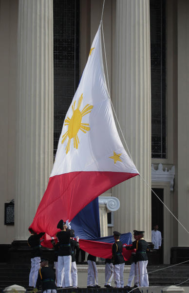 Honor guards prepare the Philippine flag before ceremonies to mark the 115th Philippine Independence Day at Liwasang Bonifacio, a square named after Filipino revolutionary leader Andres Bonifacio, in Manila, Philippines on Wednesday June 12, 2013. Aquino III vowed Wednesday his country will not back down from any challenge to its sovereignty and territory amid a sea dispute with China. (AP Photo/Aaron Favila)