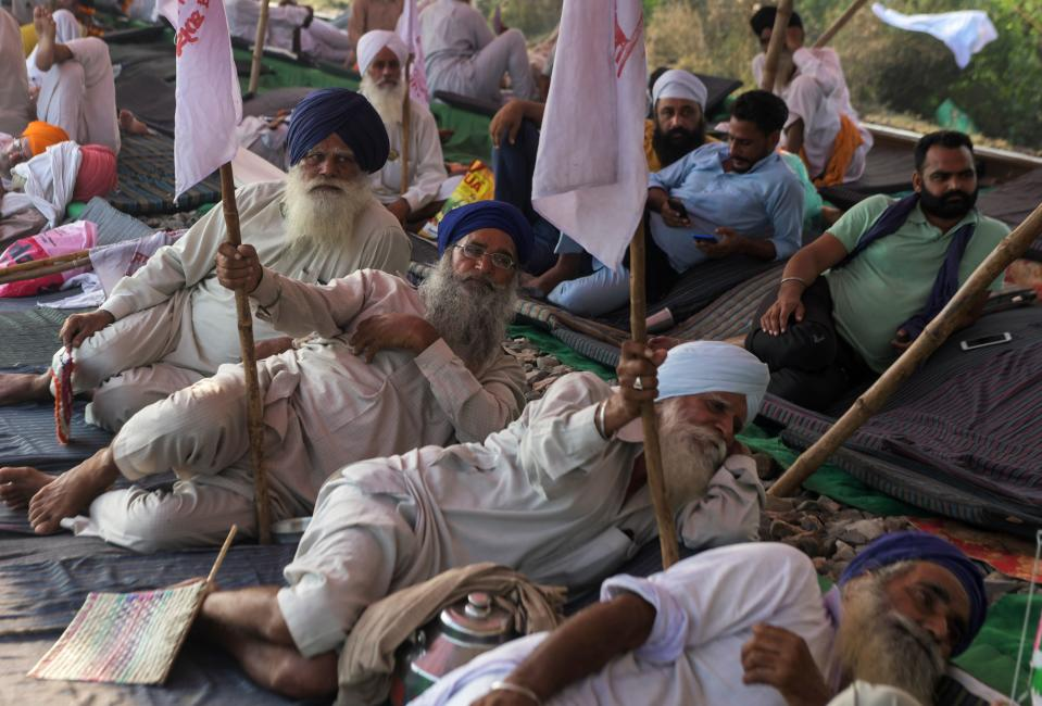 Farmers block train tracks during a nationwide farmers' strike following the recent passing of agriculture bills in the Lok Sabha (lower house), at Devi Dasspura village some 25 kms from Amritsar on September 25, 2020. (Photo by NARINDER NANU/AFP via Getty Images)