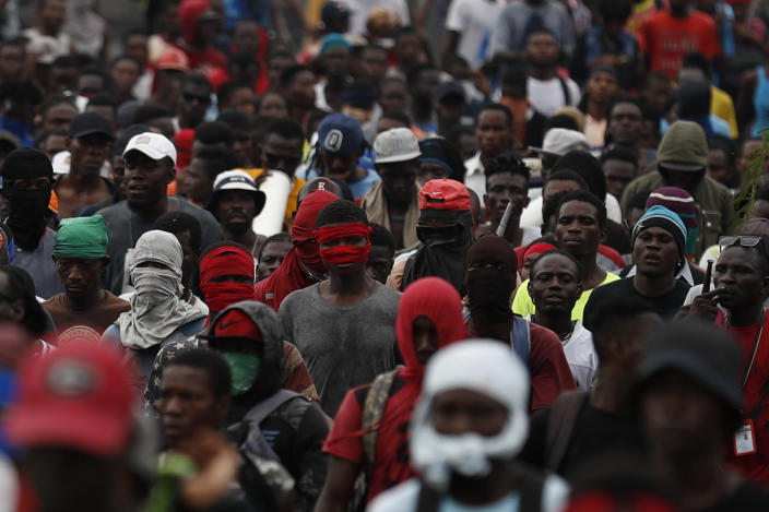 Protestors calling for the resignation of Haitian President Jovenel Moise march toward the National Palace before they were stopped by police in Port-au-Prince, Haiti, Tuesday, Oct. 1, 2019. While there were sporadic demonstrations on Tuesday, another protest scheduled for Wednesday threatened to once again paralyze Haiti's capital and nearby communities, which have endured violent demonstrations for nearly a month as anger grows over corruption, spiraling inflation and dwindling supplies of food and gasoline. (AP Photo/Rebecca Blackwell)