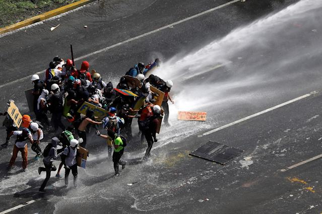<p>Demonstrators are hit by a jet of water during clashes at a march to the state ombudsman's office in Caracas, Venezuela, May 29, 2017. (Carlos Garcia Rawlins/Reuters) </p>