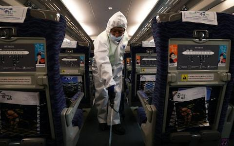 A disinfection worker sprays anti-septic solution in an train in Seoul, South Korean, amid rising public concerns over the spread of China's Wuhan Coronavirus - Credit:  Chung Sung-Jun/ Getty Images AsiaPac