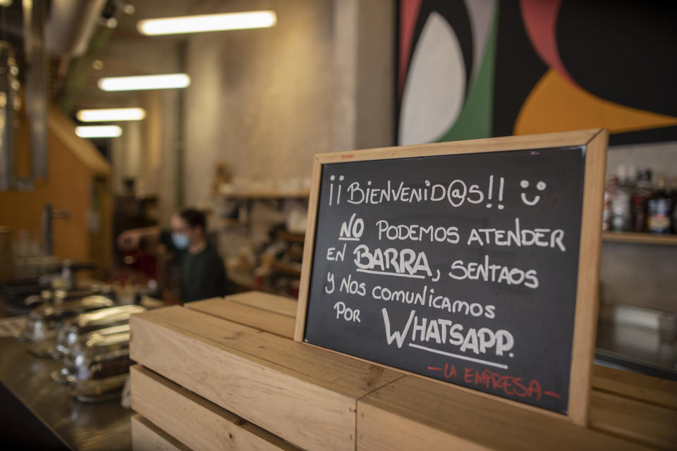 """A banner reading in Spanish: """"Welcome, we cannot serve in the bar. Sit down and we communicate by WhatsApp"""" is pictured at La Francachela restaurant in Madrid, Spain, Friday, March 26, 2021. Experimenting with cutting back one workday per week is about to go nationwide in Spain. A 3-year pilot project will be using 50 million euros ($59 million) from the European Union's massive coronavirus recovery fund to compensate companies as they resize their workforce or reorganize production workflows to adapt to a 32-hour working week. (AP Photo/Manu Fernandez)"""