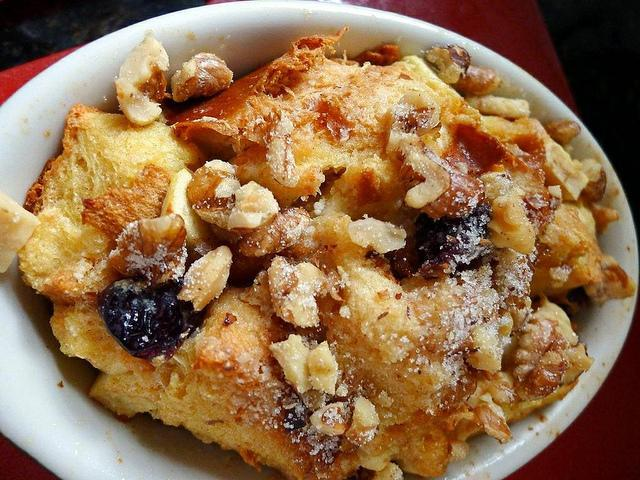 """<p>Bread pudding is an easy dessert to make with ingreadients easily found in kitchens like milk, bread, eggs & little sugar. To make bread pudding, trim the crust of 6-7 bread slices & cut into small triangles & butter the slices. Arrange the slices in an oven proof dish & add some raisins & chopped almonds between layers of bread. In a mixing bowl, add some condensed milk, two beaten eggs, 2 cups of milk & mix well. Adjust sugar if needed. Pour this mix on the bread slices & bake at 180 degrees in oven for 20-25 mins till golden brown on top. """"Creative Commons Ramekin of Bread Pudding"""" by Lori L. Stalteri is licensed under CC BY 2.0 </p>"""