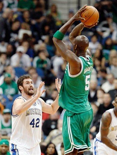 Boston Celtics forward Kevin Garnett (5) makes a three-point basket as Minnesota Timberwolves forward Kevin Love (42) defends during the first quarter of an NBA basketball game on Friday, March 30, 2012, in Minneapolis. (AP Photo/Genevieve Ross)