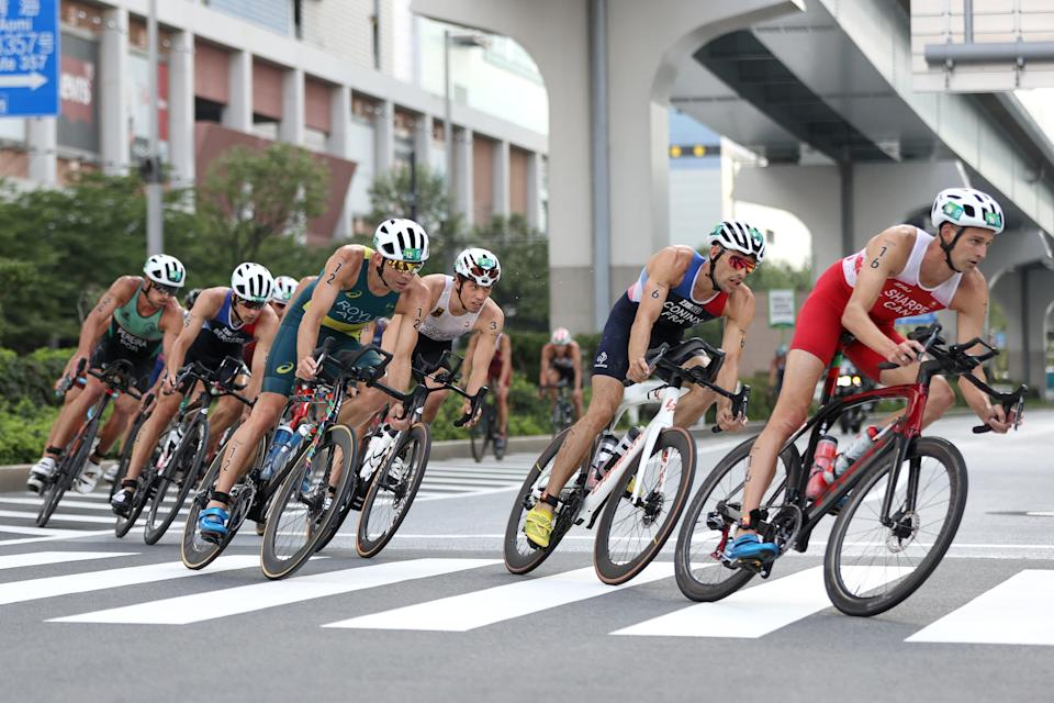 <p>Canada's Matthew Sharpe rides ahead of France's Dorian Coninx, Australia's Aaron Royle, Germany's Justus Nieschlag and other competitors during the men's individual triathlon competition at the Odaiba Marine Park, in Tokyo, on July 26, 2021 during the Tokyo 2020 Olympic Games. (Photo by Cameron Spencer / POOL / AFP) (Photo by CAMERON SPENCER/POOL/AFP via Getty Images)</p>