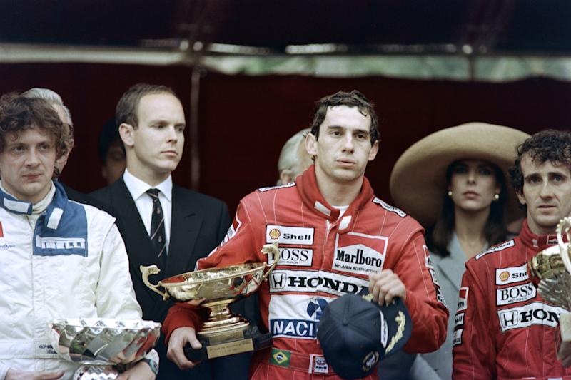 Brazilian Ayrton Senna holds his trophy as he is flanked by second placed teammate Alain Prost of France (R) and third placed Stephano Mondena (L) after winning the Monaco F1 Grand Prix at the wheel of his McLaren-Honda on May 7, 1989, as Prince Albert (2nd L) and Princess Caroline (2nd R) look on. (Photo by AFP) (Photo credit should read DOMINIQUE FAGET,MICHEL GANGNE,GERARD JULIEN,PASCAL PAVANI/AFP via Getty Images)