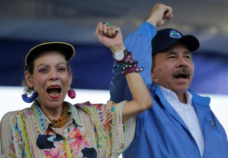 Nicaraguan President Daniel Ortega and his wife, Vice-President Rosario Murillo, raise their fists during the commemoration of the 51st anniversary of the Pancasan guerrilla campaign in Managua, on August 29, 2018