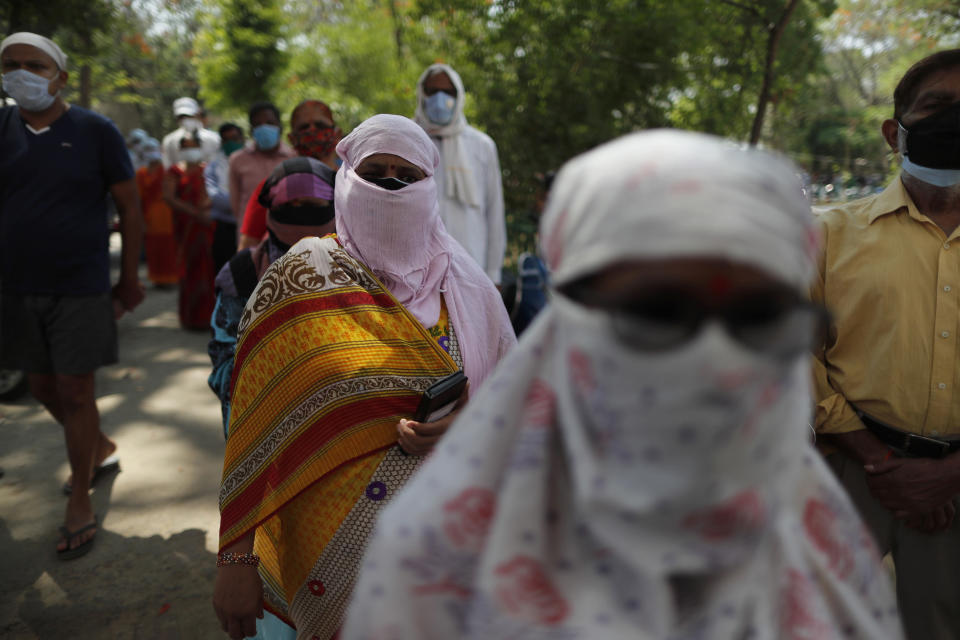 Indians cover their faces as a precaution against the coronavirus line up to receive the vaccine for COVID-19 at a medical college in Prayagraj, India, Saturday, May 8, 2021. Two southern states in India became the latest to declare lockdowns, as coronavirus cases surge at breakneck speed across the country and pressure mounts on Prime Minister Narendra Modi's government to implement a nationwide shutdown. (AP Photo/Rajesh Kumar Singh)