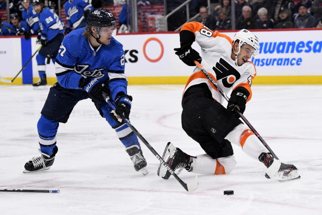 Philadelphia Flyers' Morgan Frost (48) clears the puck past Winnipeg Jets' Nikolaj Ehlers (27) during second period NHL hockey action in Winnipeg, Manitoba on Sunday Dec. 15, 2019. (Fred Greenslade/The Canadian Press via AP)