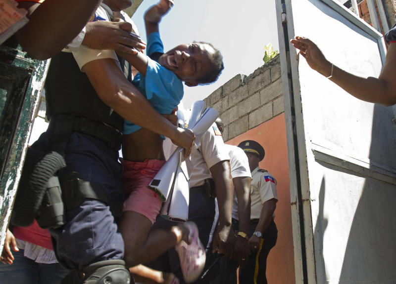 An orphan reacts as she is carried away by a police officer during the closure of the Son of God orphanage in Port-au-Prince, Haiti, Friday, Oct. 21, 2011.  The orphanage, whose director was accused by U.S. missionaries of not feeding children and selling donated goods,  was closed Friday in a rare crackdown by Haitian authorities. Police officers and child welfare officials sealed off the unpaved street in front of the Son of God orphanage and the children who lived there were loaded into a UNICEF bus and taken to new homes. (AP Photo/Dieu Nalio Chery)