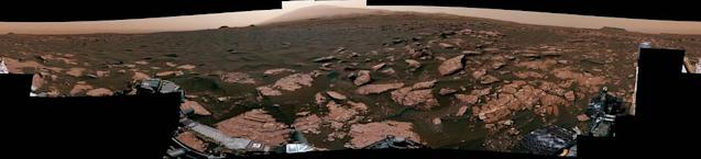 """<p>This 360-degree mosaic from the Mast Camera (Mastcam) on NASA's Curiosity Mars rover looks out over a portion of the Bagnold Dunes, which stretch for several miles. From early February to early April 2017, the rover examined four sites near linear dunes for comparison with what it found in late 2015 and early 2016 during its investigation of crescent-shaped dunes. This two-phase campaign is the first close-up study of active dunes anywhere other than Earth.<br> The dark, rippled surface of a linear dune is visible at the center of the view and receding into the distance to the left. The bedrock of the Murray formation, made from sediments deposited in lakes billions of years ago, is in the foreground, along with some components of the rover. The location, called """"Ogunquit Beach,"""" is on the northwestern flank of lower Mount Sharp. (Photo: NASA/JPL-Caltech/MSSS) </p>"""