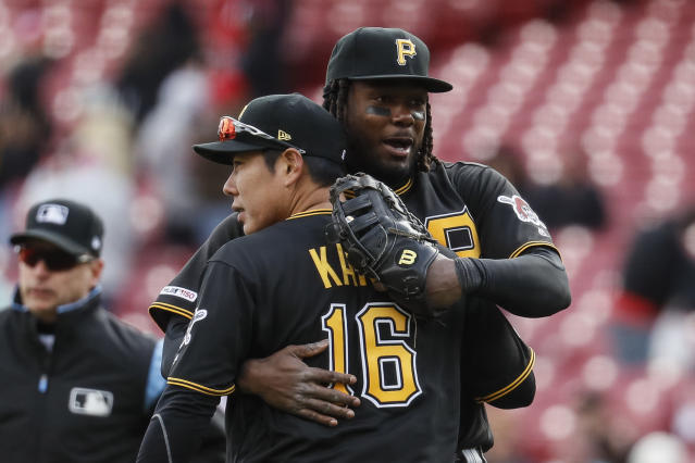Pittsburgh Pirates shortstop Jung Ho Kang (16) and first baseman Josh Bell, right, celebrate after closing the ninth inning of a baseball game against the Cincinnati Reds, Sunday, March 31, 2019, in Cincinnati. (AP Photo/John Minchillo)