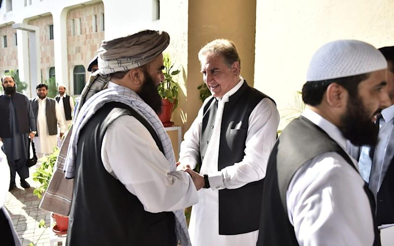 Pakistan's Foreign Minister Shah Mehmood Qureshi (centre R) receives members of the Taliban delegation at the Pakistan Foreign Ministry in Islamabad on October 3 - AFP