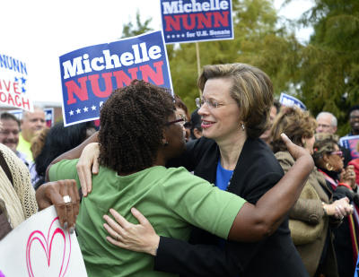Democratic candidate for U.S. Senate Michelle Nunn, right, participates in a rally before casting her own ballot in early voting at the Adamsville Recreation Center in Fulton County on Wednesday, Oct. 15, 2014 in Atlanta. Nunn is running against Republican David Perdue. (AP Photo/David Tulis)