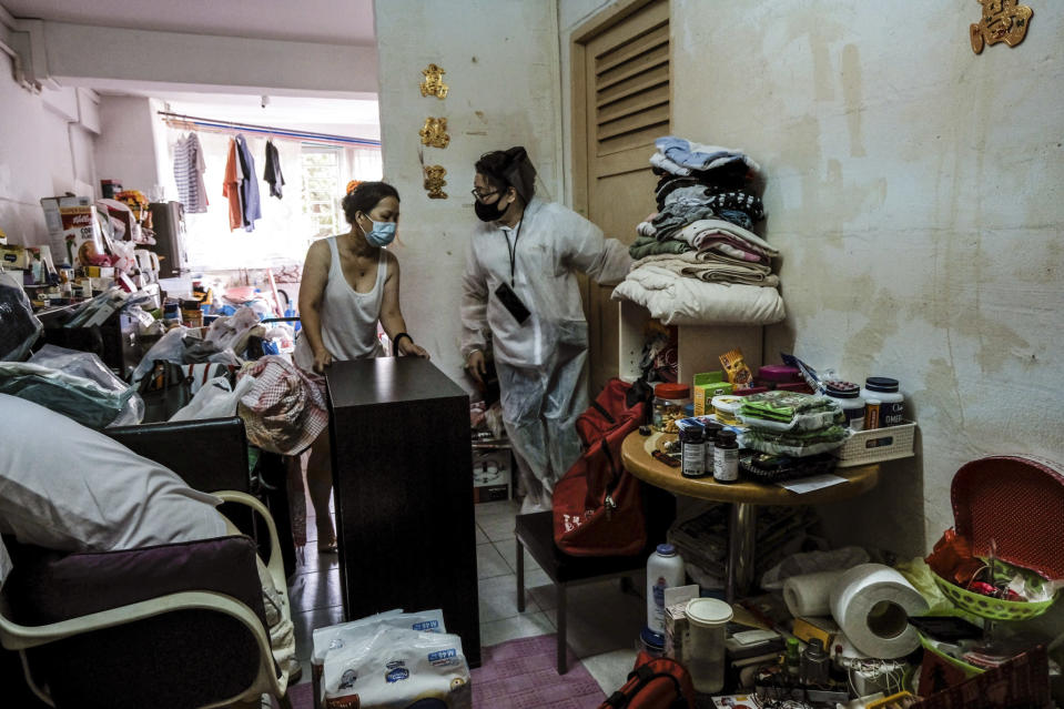 Keeping Hope Alive founder Fion Phuatalks, RIGHT, talks to a resident of a cluttered rental flat Sunday, Oct. 4, 2020 in Singapore. Members of the volunteer group conduct weekend door-to-door visits to deliver goods or provide services to people in need. (AP Photo/Ee Ming Toh)