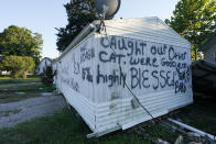 A damaged home with messages painted on it sits empty Sept. 27, 2021, in Waverly, Tenn. After a devastating flood hit Aug. 21, the town of just over 4,000 people faces a dilemma. More than 500 homes and 50 businesses were damaged. That will likely result in massive revenue losses while the city spends millions on cleanup and repairs. If those homes and businesses don't return, the town could die a lingering death. But if they build back along the creek, they could be risking another disaster. (AP Photo/Mark Humphrey)