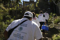 A medical team climbs uneven worn steps up a hillside to reach the home of Maria del Socorro Fuentes Chirino, 64, to administer a shot of the AstraZeneca coronavirus vaccine, in rural San Lorenzo Acopilco on the outskirts of Mexico City, Thursday, Feb. 18, 2021. Mexico City's health department is sending teams of medical workers to give in-home vaccinations for elderly residents unable to reach vaccination centers. (AP Photo/Rebecca Blackwell)