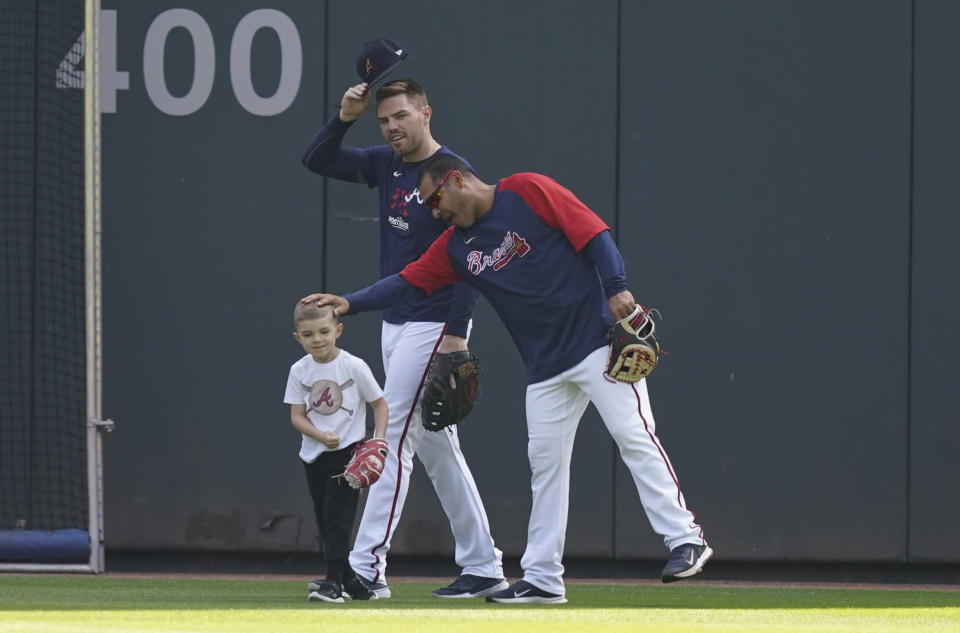 Atlanta Braves batting practice pitcher Tomas Perez reaches out to Charlie, son of Braves' Freddie Freeman, center, during a workout ahead of the NLCS playoff baseball game, Thursday, Oct. 14, 2021, in Atlanta. (AP Photo/Brynn Anderson)