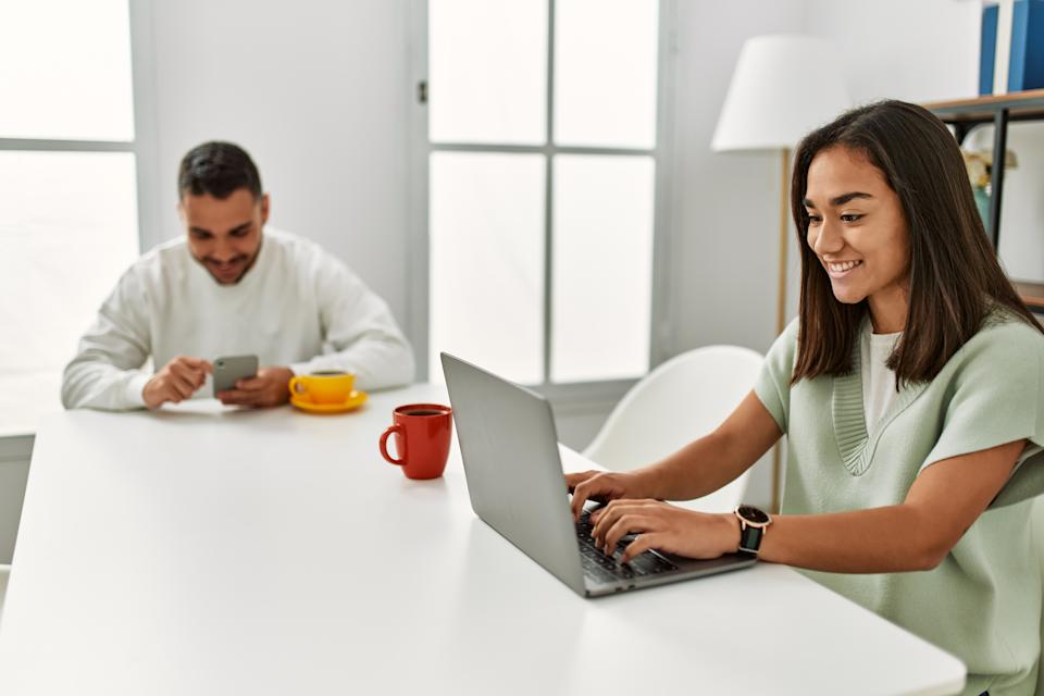 Young latin couple using laptop and smartphone drinking coffee at home.