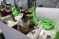 Workers wearing face mask and face shield to help curb the spread of the new coronavirus, sew behind white partition surrounding their sewing tables as they work at a garment factory Thursday, May 28, 2020, at Industrial Zone in Yangon, Myanmar. Despite a poor public health infrastructure and crowded urban areas, Myanmar has reported a surprising low number of COVID-19 cases, with just a little over 200 confirmed and a few deaths. (AP Photo/Thein Zaw)
