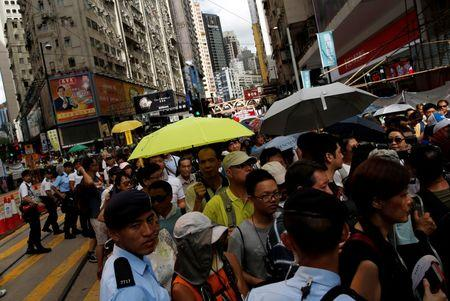 A protester carries a yellow umbrella, symbolizing the 2014 Occupy Central pro-democracy movement, during a protest march on the day marking the 19th anniversary of Hong Kong's handover to Chinese sovereignty from British rule, in Hong Kong, China July 1, 2016. REUTERS/Tyrone Siu