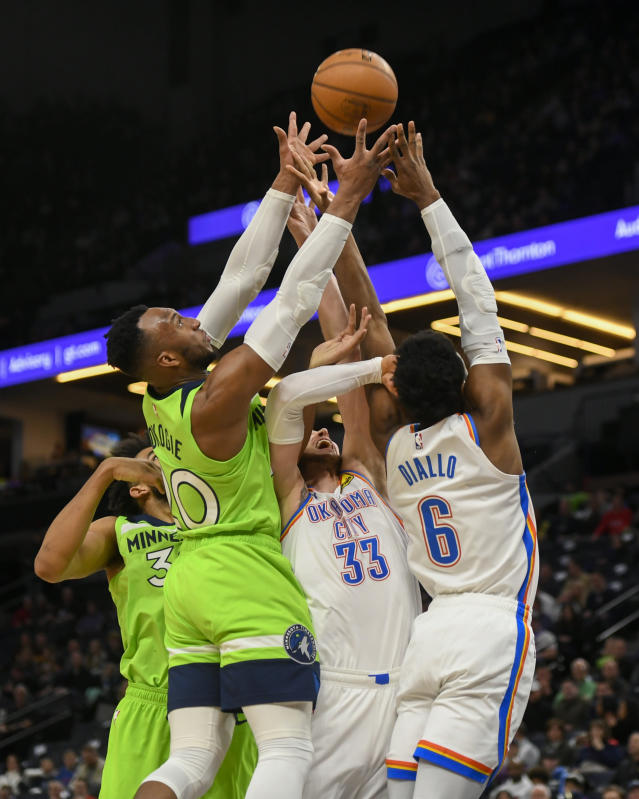 Minnesota Timberwolves center Karl-Anthony Towns, from left, Timberwolves guard Josh Okogie, Oklahoma City Thunder forward Mike Muscala and Thunder guard Hamidou Diallo go up for a rebound during the first half of an NBA basketball game Saturday, Jan. 25, 2020, in Minneapolis. (AP Photo/Craig Lassig)