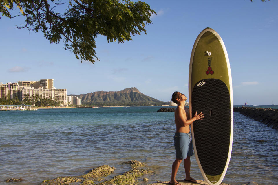 In this photo provided by Yoko Liriano, Bryant de Venecia poses for a photo with his paddleboard in Honolulu, Wednesday, Nov. 11, 2020. He started stand-up paddle-boarding when there were fewer tourists coming to Hawaii during the pandemic. He's among the Hawaii residents feeling ambivalence toward tourists returning now that the state is allowing incoming travelers to bypass a 14-day quarantine with a negative COVID-19 test. (Yoko Liriano via AP)