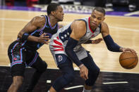 Sacramento Kings guard De'Aaron Fox (5) defends Washington Wizards guard Russell Westbrook (4) as he looks to make a play during the second quarter of an NBA basketball game in Sacramento, Calif., Wednesday, April 14, 2021. (AP Photo/Hector Amezcua)