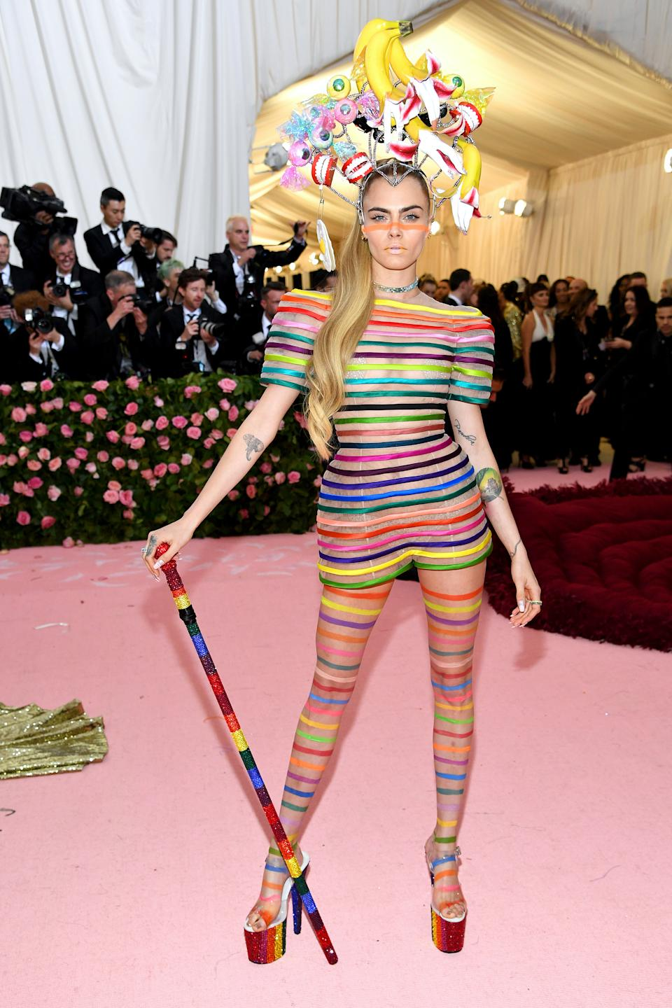 Model and actress Cara Delevingne attended the Met Gala in a striped playsuit, complete with a headpiece featuring both fake teeth and bananas. Photo: Getty Images