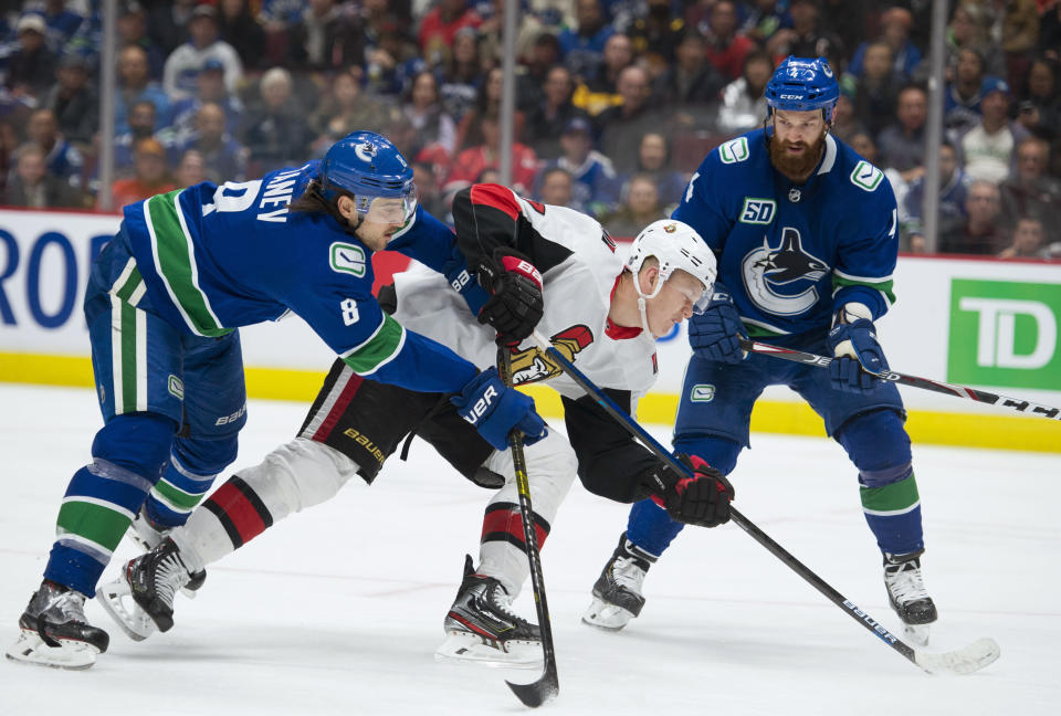 Ottawa Senators left wing Brady Tkachuk (7) fights for control of the puck with Vancouver Canucks defensemen Christopher Tanev (8) and Jordie Benn (4) during the third period of an NHL hockey game Tuesday, Dec. 3, 2019, in Vancouver, British Columbia. (Jonathan Hayward/The Canadian Press via AP)