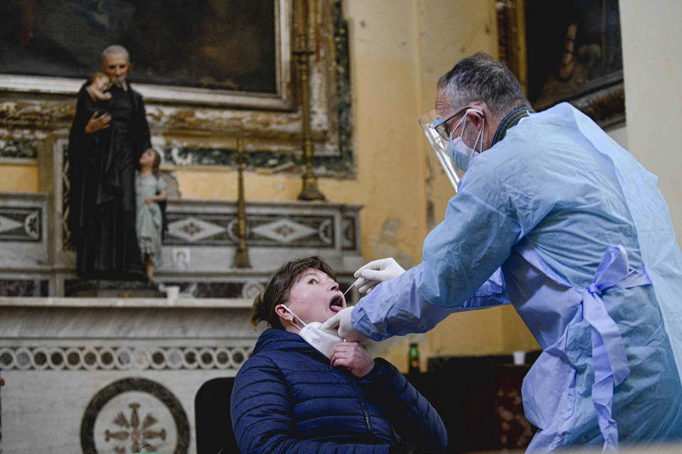 """A medical operator performs COVID-19 test swabs in the Church of San Severo Outside the Walls, in the heart of Naples, Italy, Wednesday, Nov. 18, 2020. An initiative of """"Sanita' Diritti Salute"""" association and the San Gennaro Foundation, aimed at helping those who cannot afford the cost of a private test, also allows, in the best tradition of Naples, those who want to pay 18 euros for a """"suspended swab"""", to be taken by somebody else, exactly as it happens for the famous Neapolitan """"suspended coffee"""". (Alessandro Pone /LaPresse via AP)"""