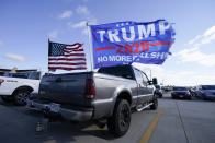 Flags fly over a pickup truck outside a President Donald Trump campaign rally at Dubuque Regional Airport, Sunday, Nov. 1, 2020, in Dubuque, Iowa. (AP Photo/Charlie Neibergall)
