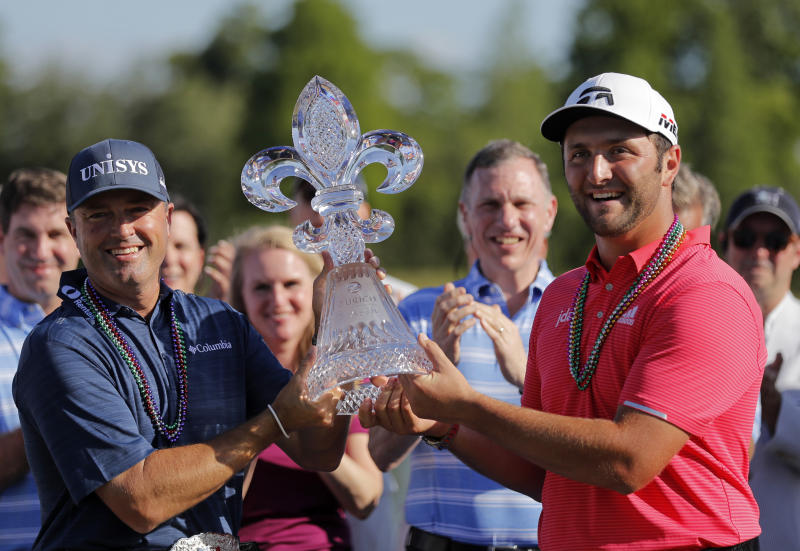 Ryan Palmer, left, and Joh Rahm hold their tournament trophy after winning the PGA Zurich Classic golf tournament at TPC Louisiana in Avondale, La., Sunday, April 28, 2019. (AP Photo/Gerald Herbert)