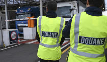 FILE - In this Tuesday, Sept. 17, 2019 file photo, French custom officers observe trucks on their way to Great Britain, during a test in case of a no deal Brexit, at the exit of the Channel tunnel in Calais, northern France. Britain and the European Union have struck a provisional free-trade agreement that should avert New Year chaos for cross-border traders and bring a measure of certainty for businesses after years of Brexit turmoil. (Denis Charlet, Pool via AP, File)