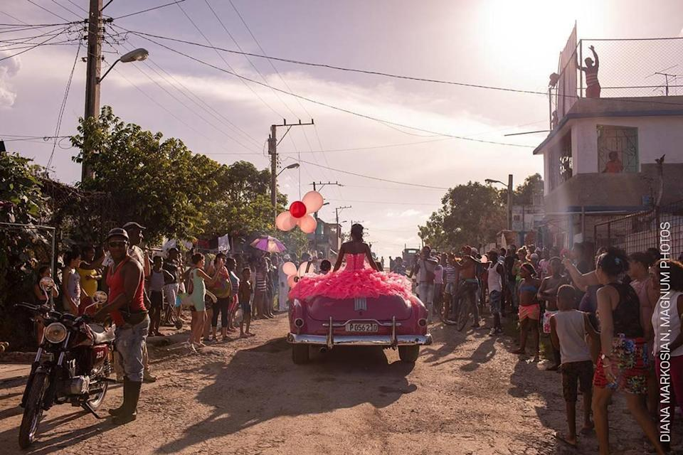 <p>Pura rides around her neighborhood in a pink 1950s convertible, as the community gathers to celebrate her fifteenth birthday, in Havana, Cuba. (Diana Markosian) </p>