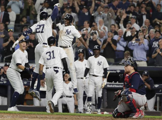 New York Yankees' Giancarlo Stanton (27) celebrates with teammates Aaron Judge, Aaron Hicks (31) and Didi Gregorius after hitting a grand slam during the fourth inning of a baseball game Thursday, Sept. 20, 2018, in New York. At right is Boston Red Sox catcher Christian Vazquez. (AP Photo/Frank Franklin II)